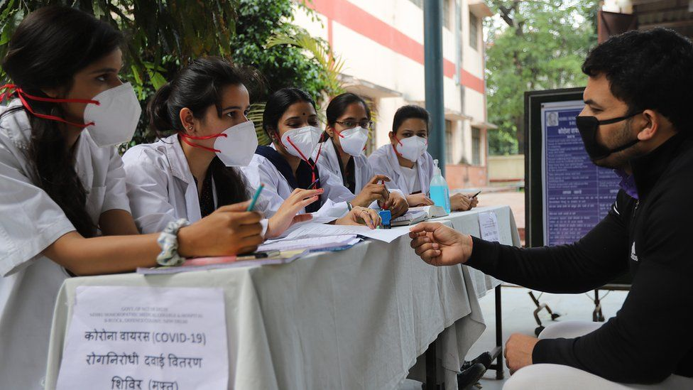A man speaks to healthcare workers in India