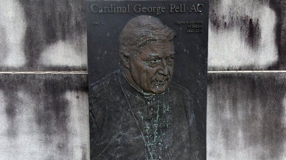"""A faded plaque depicts George Pell below the words: """"Cardinal George Pell AC"""""""