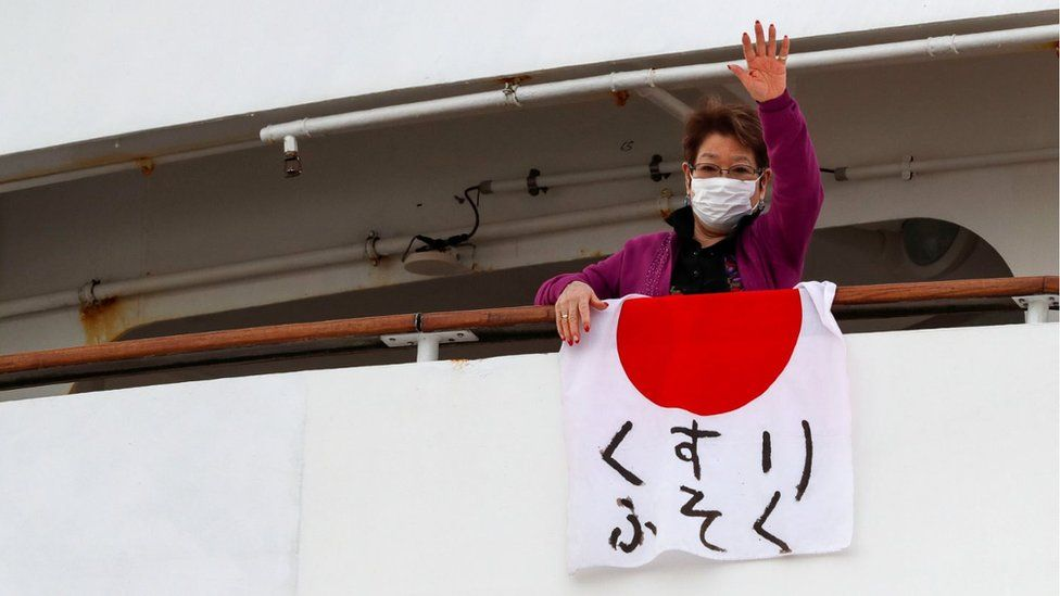 "Woman waving a flag reading ""shortage of medicine"" from the ship"