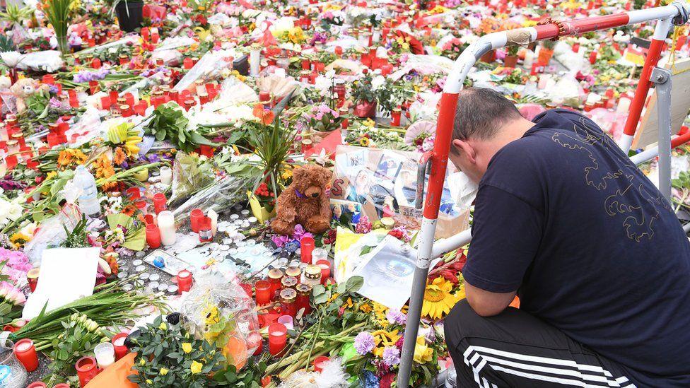 Man prays at memorial