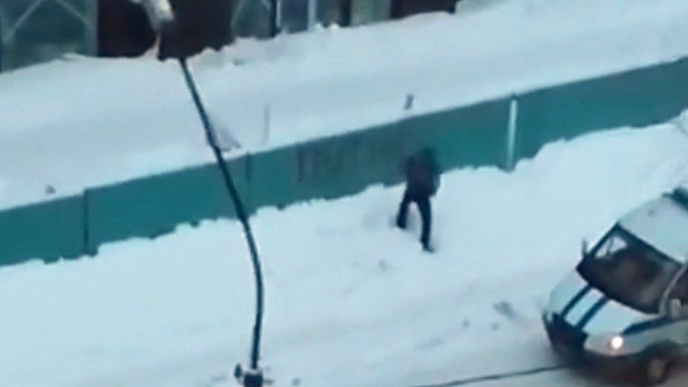 Still from YouTube video of a man allegedly painting the word 'Putin' on a fence