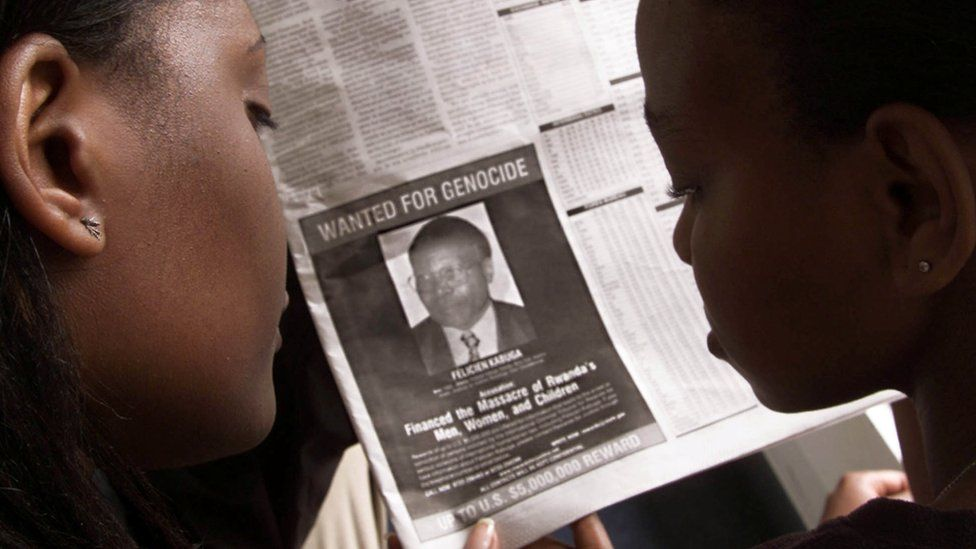 Readers look at a newspaper June 12, 2002 in Nairobi carrying the photograph of Rwandan Felicien Kabuga wanted by the United States