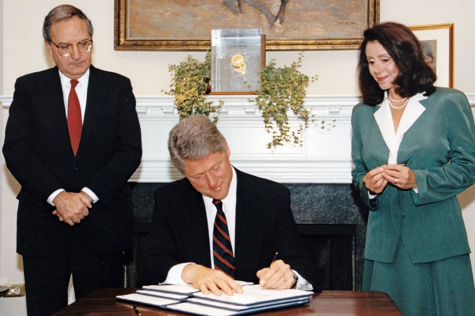 US Senate Majority Leader George Mitchell (left) and US Representative Nancy Pelosi watch as President Clinton (centre) signs an executive order