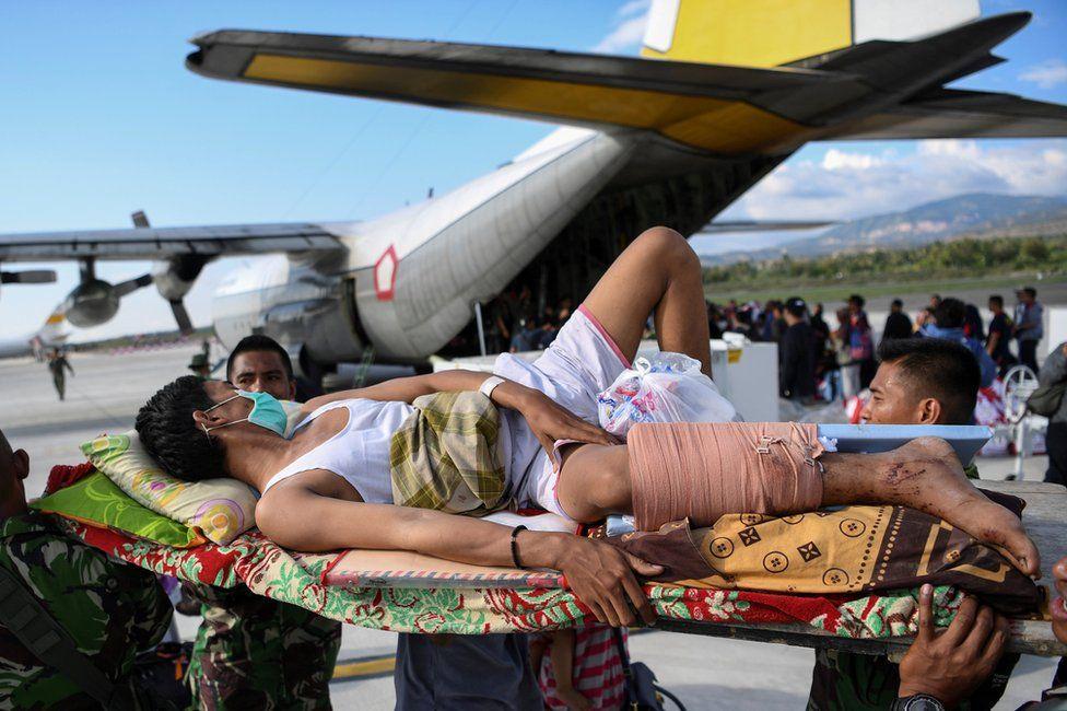 An injured man awaits evacuation at Palu airport, 30 September