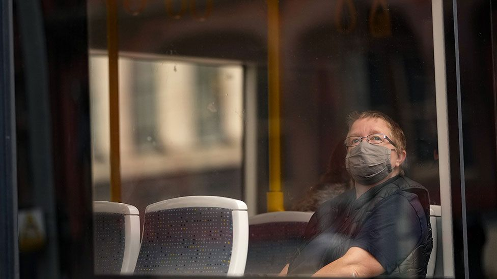 A man wearing a mask sits on a bus in Manchester