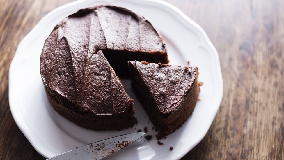 Cutting a chocolate cake into pieces