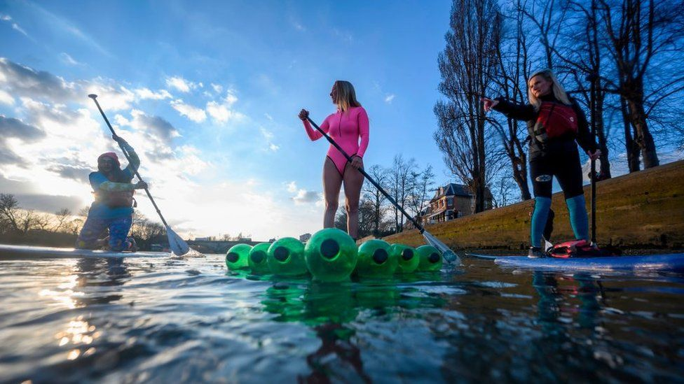 Climate change protesters surfing on the River Thames in March to raises awareness on the need to combat climate change