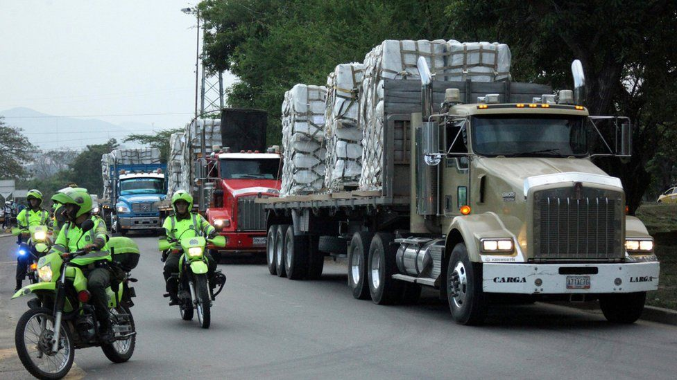 Police escort trucks arriving at a warehouse where humanitarian aid for Venezuela will be stored near the Tienditas bridge between Colombia and Venezuela, Feb. 16, 2019