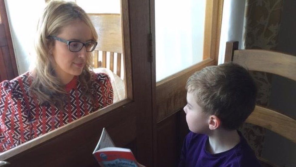 Catherine and son reading through window