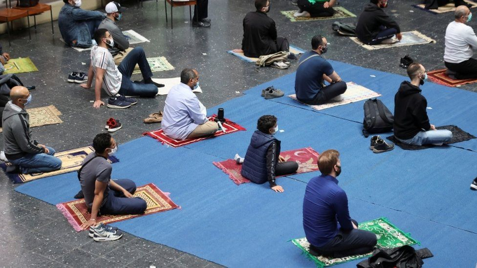 Worshippers sit on their prayer mats during Friday prayers at a church in Berlin
