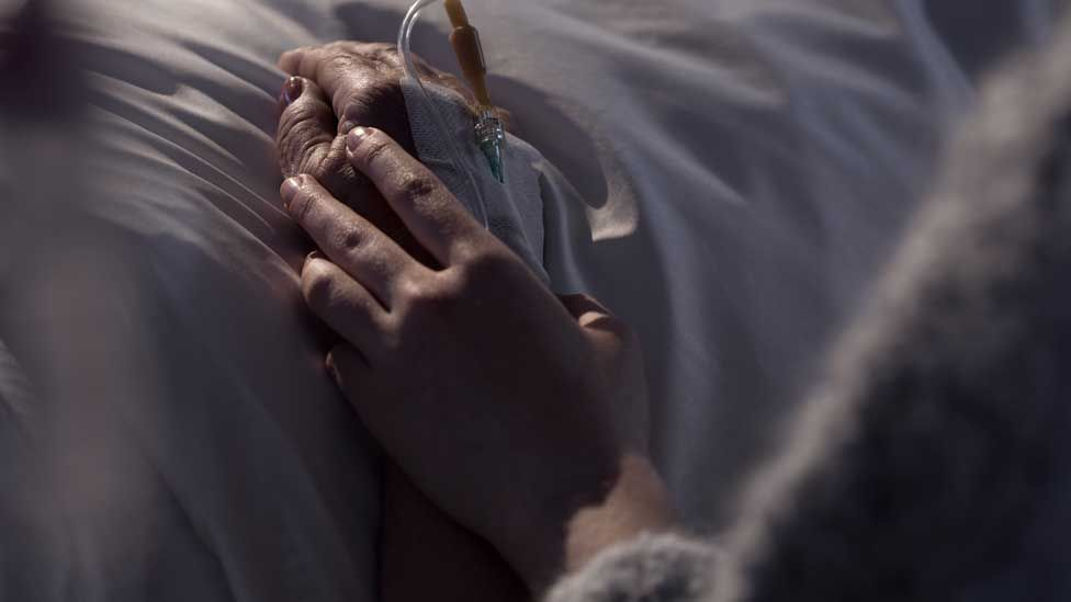 A woman's hand holding another's in a hospital bed