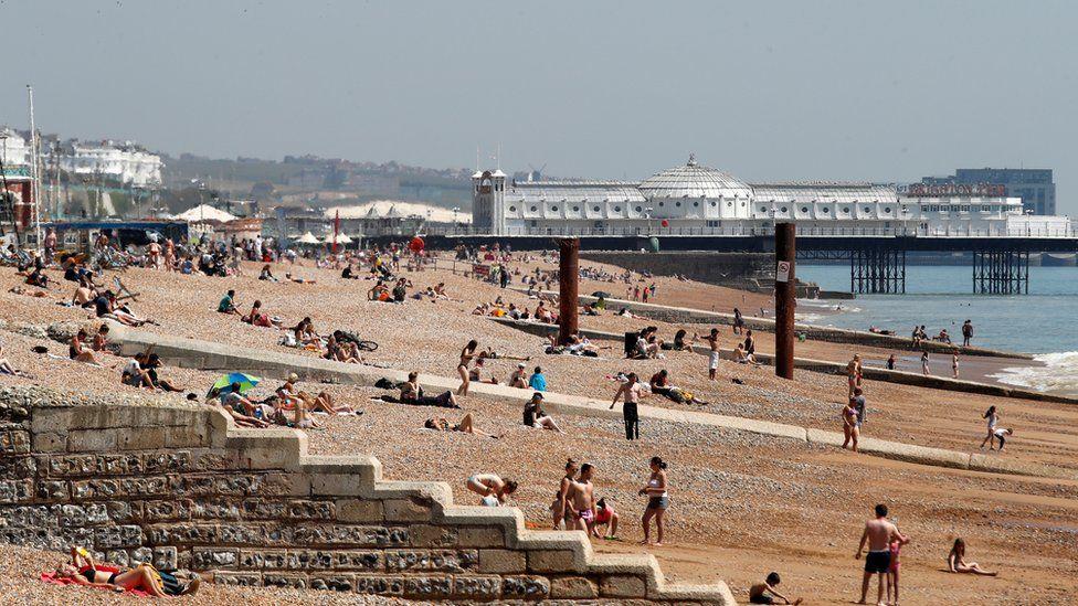 People are seen on Brighton beach following the outbreak of the coronavirus disease (COVID-19), Brighton, Britain