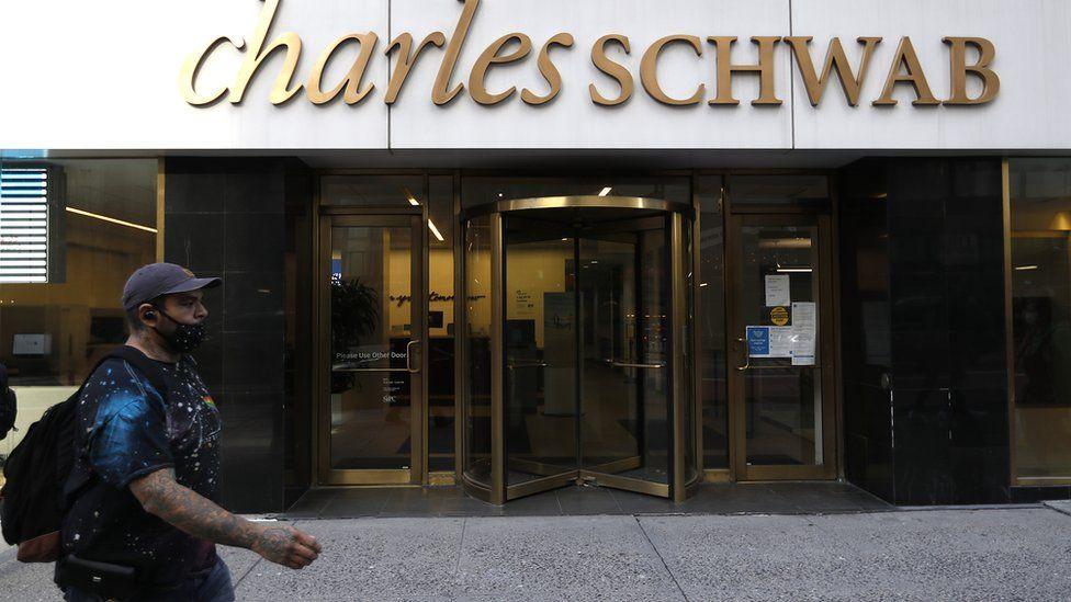 man in mask walks past Charles Schwab