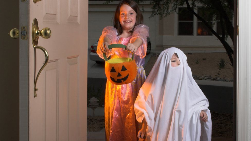 Children trick or treating on Halloween.