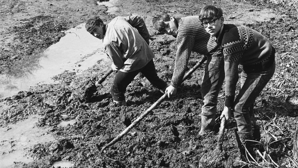 A group of boys from Gordonstoun School helping to clear the moat during restoration work at Michelham Priory near Hailsham, Sussex, 11th April 1967.