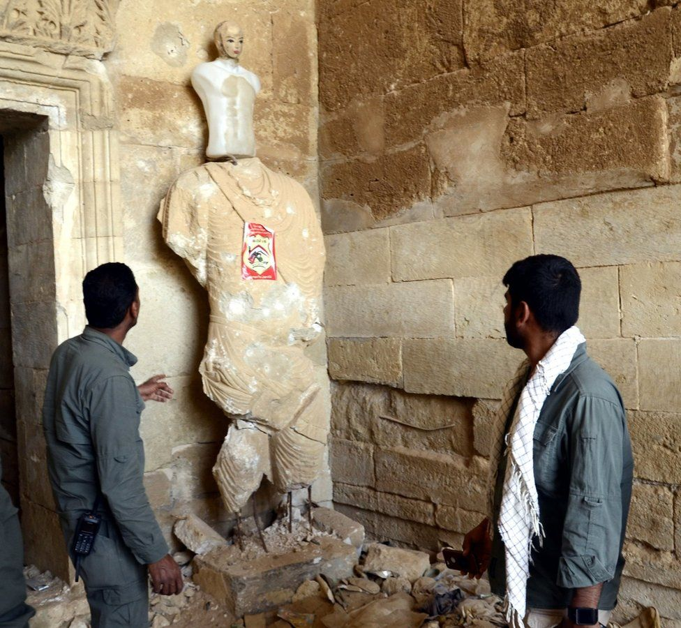 Members of the paramilitary Popular Mobilisation force inspect damage at the ancient city of Hatra in Iraq (28 April 2017)