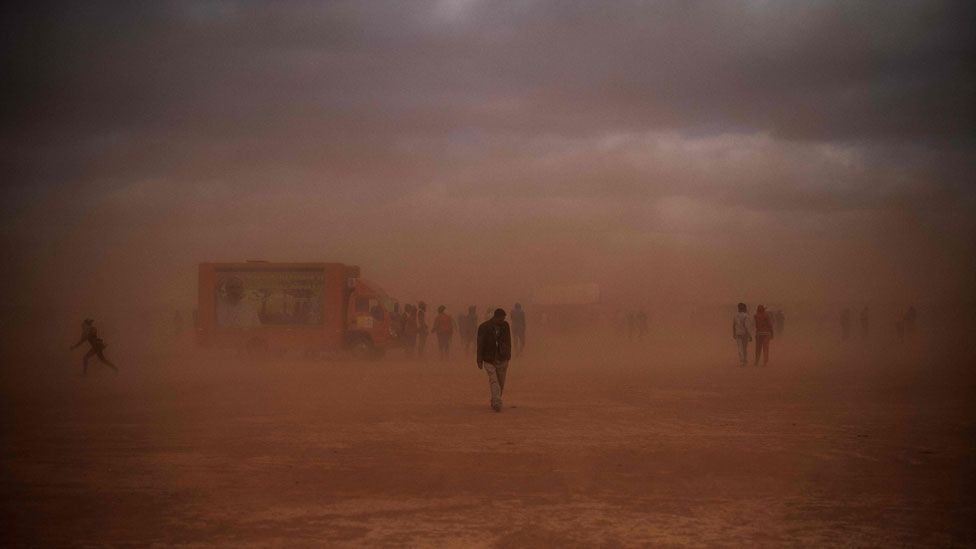 People walking to the mass in the dust
