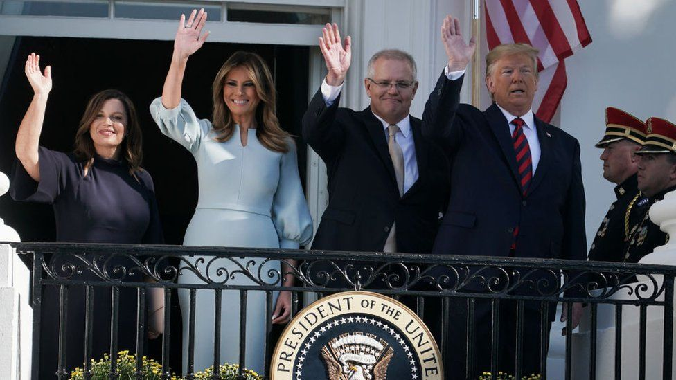 President Donald Trump and first lady Melania Trump, Australian Prime Minister Scott Morrison and his wife Jennifer Morrison wave from the White House on 20 September