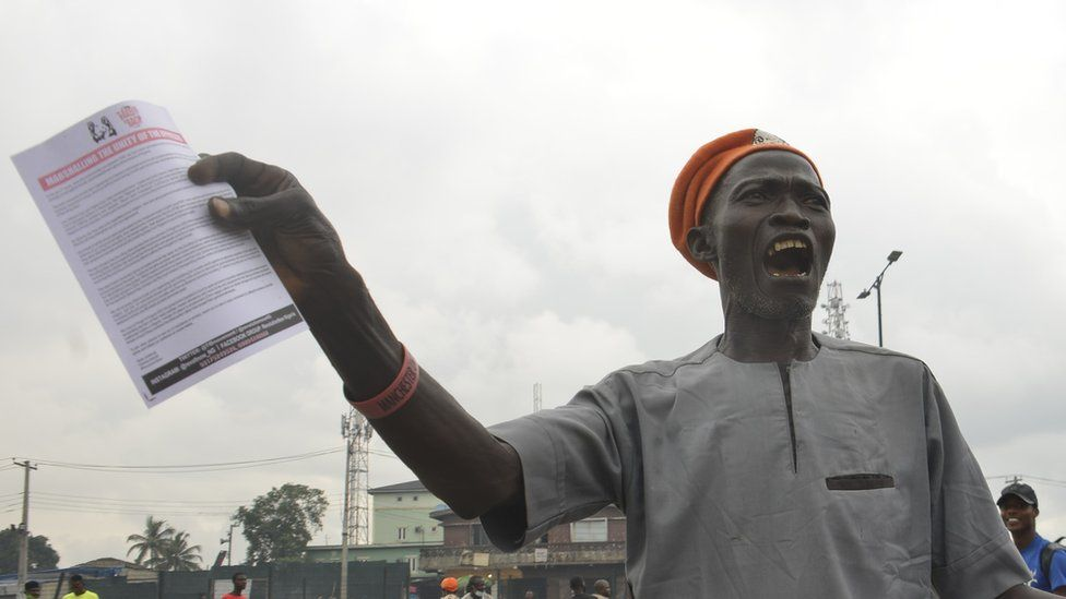 A protestor demanding the resignation of President Buhari as Nigeria marked its 61st year of independence on 1st October. He can be seen holding a leaflet and shouting on the street.