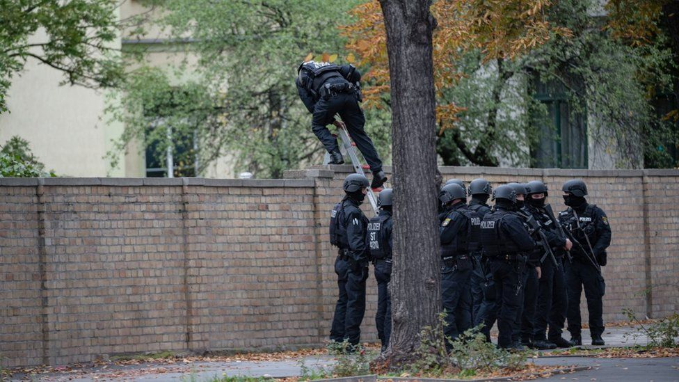 Police climb over a wall into a Jewish cemetery