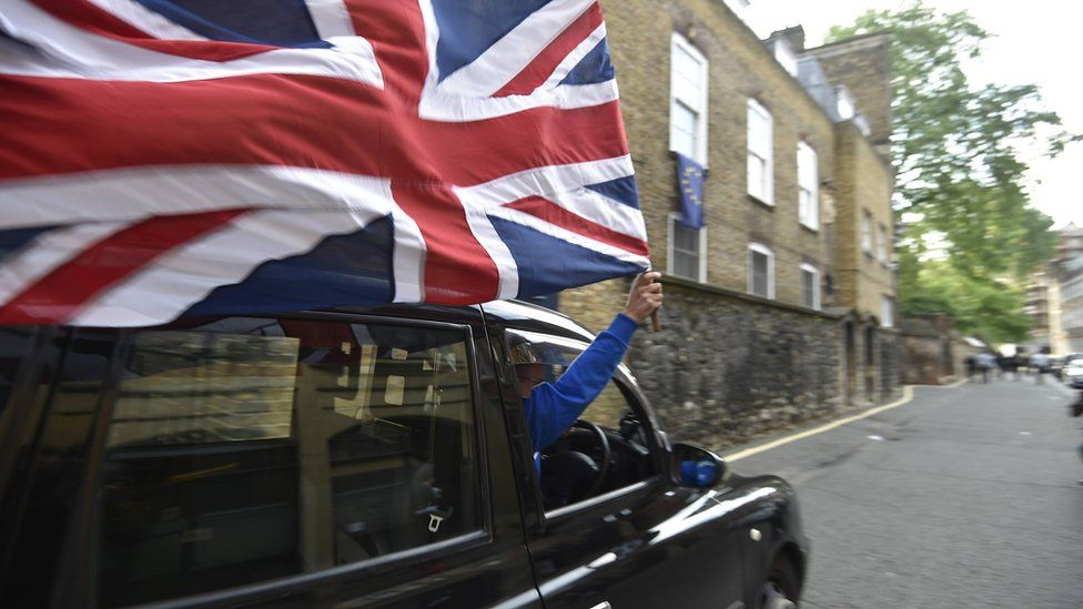A taxi driver holds a Union flag, as he celebrates following the result of the EU referendum