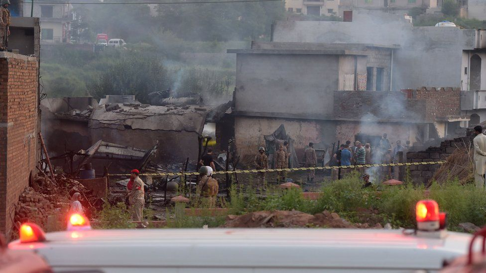 Soldiers and other personnel work at the scene where a Pakistani Army Aviation Corps aircraft crashed in Rawalpindi on July 30, 2019.