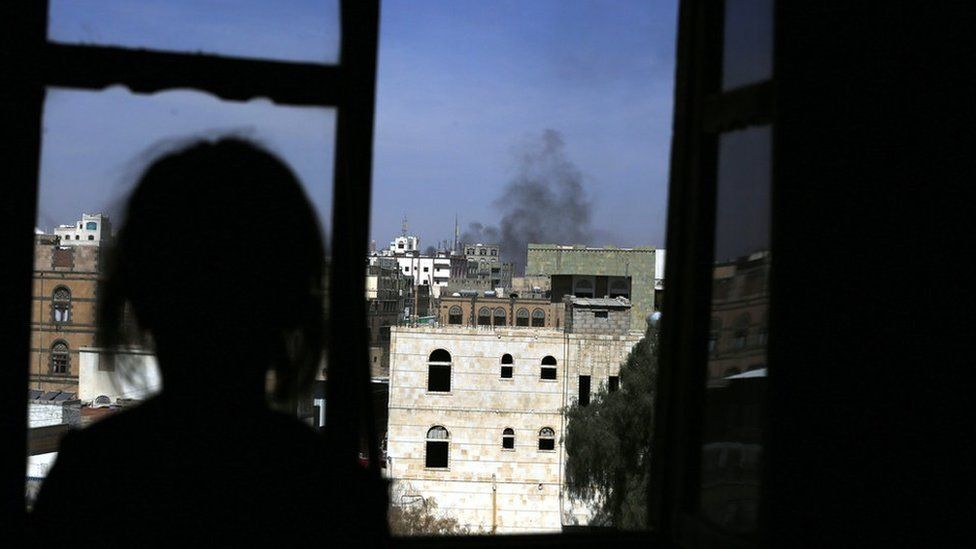 The silhouette of a girl looking out a window as plumes of smoke.