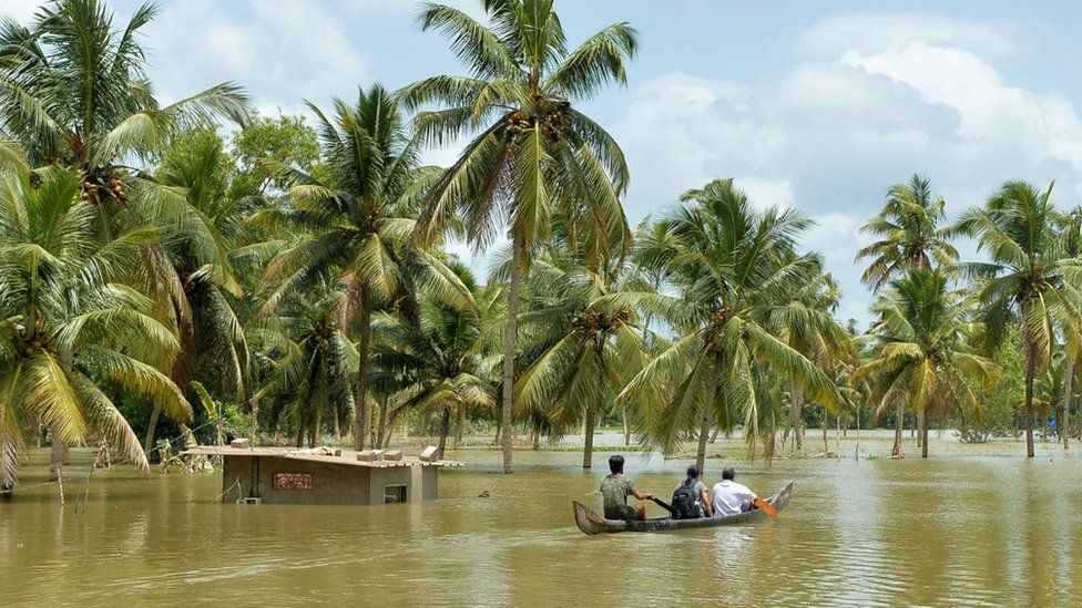 Three people riding a boat through a flooded area