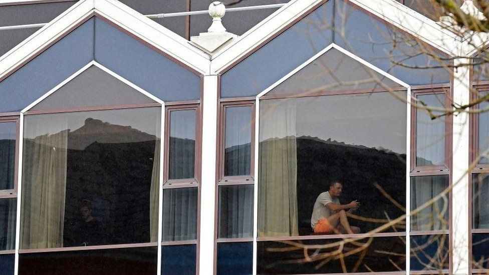 A man sits at a window of the Radisson Blu hotel at Heathrow Airport in west London
