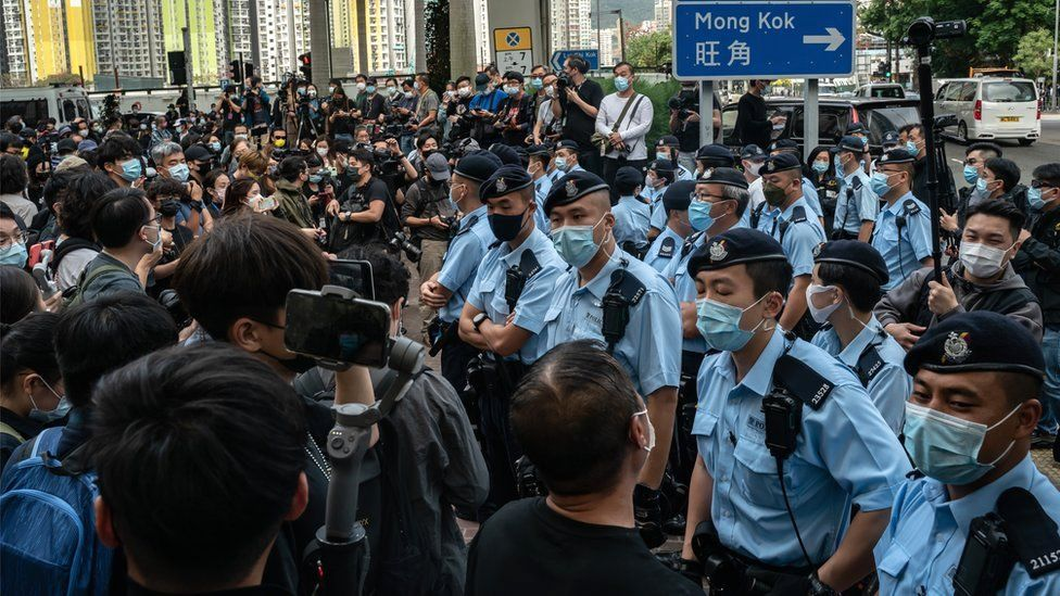 Police officers stand guard as pro-democracy supporters gather outside the West Kowloon court in Hong Kong, 1 March 2021