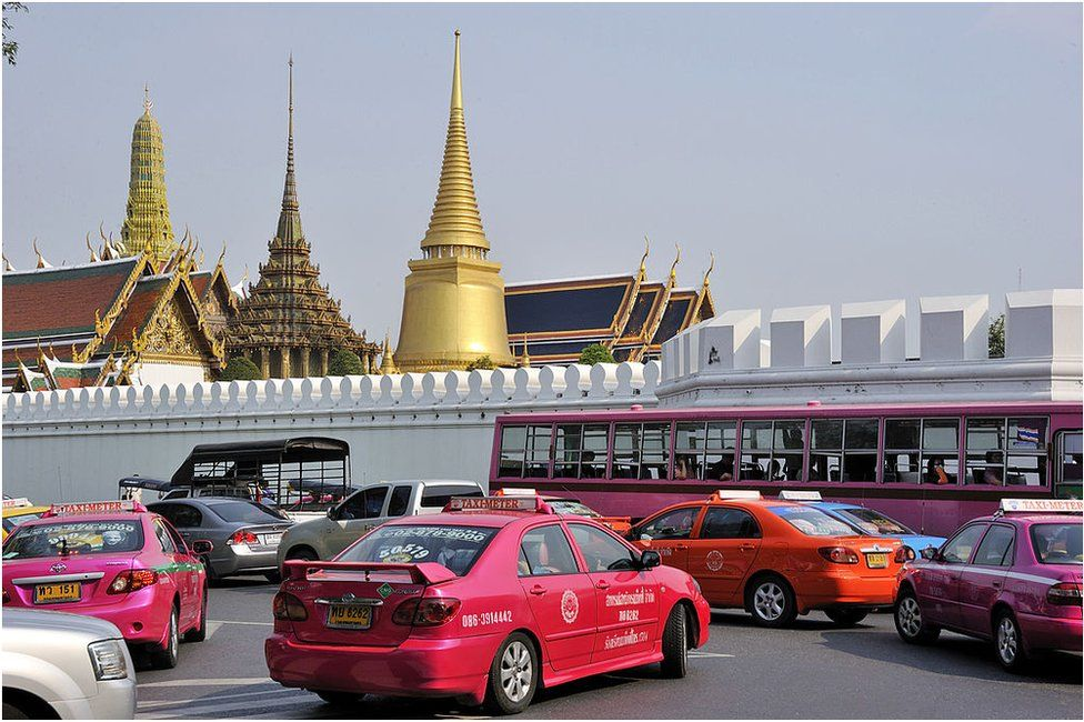 This picture taken on 19 March 2011 in Bangkok shows cars and buses parked near the Royal Palace.