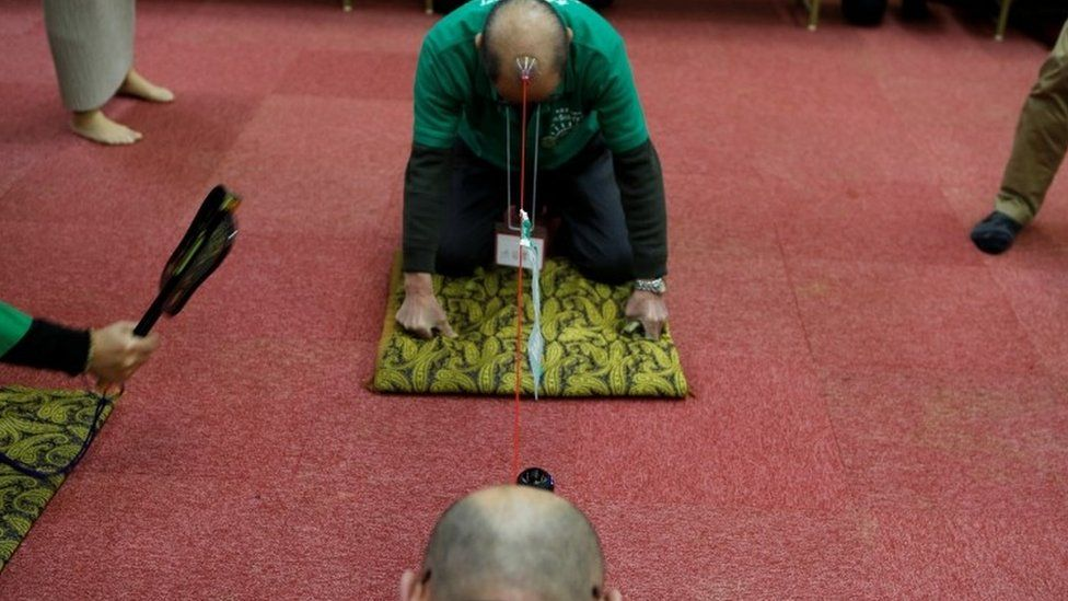 Japanese Bald Men Club members participate in a tug-of-war contest (22 February 2017)