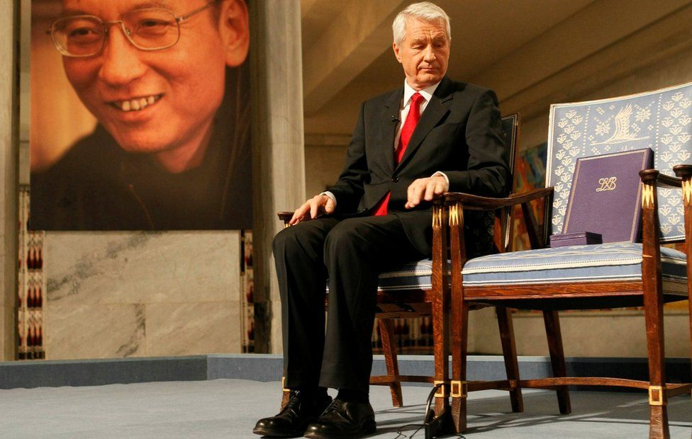 Chairman of Norwegian Nobel Committee Jagland looks down at Nobel certificate and medal on empty chair where Liu would have sat, in Oslo on 10 December 2010