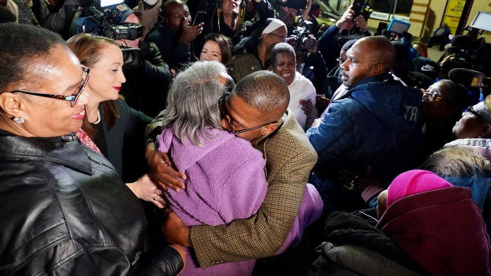 Alfred chestnut hugs his mother surrounded by a crowd