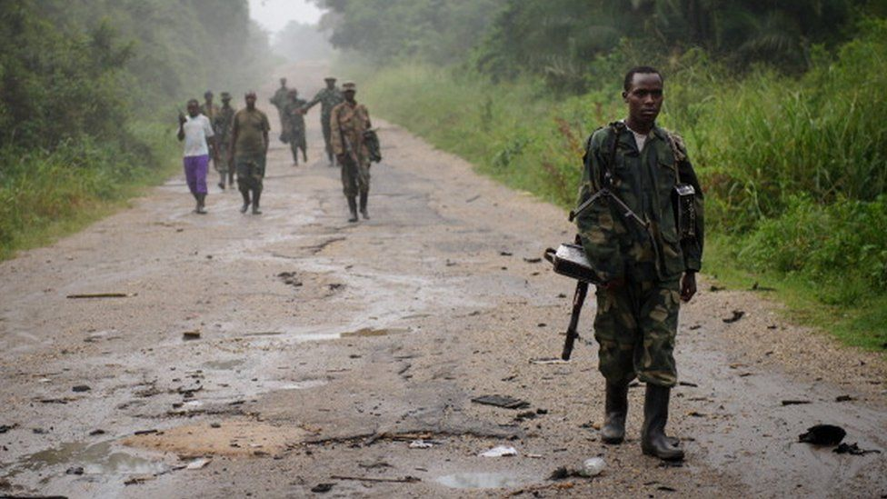 This picture taken on July 28, 2012 shows M23 rebels walking along a road through jungle in the Virunga National Park, near the village of Mabenga in the Democratic Republic of the Congo's restive North Kivu province