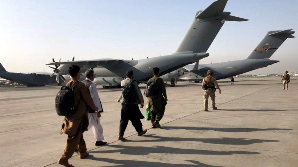 People are escorted to military planes at Kabul airport