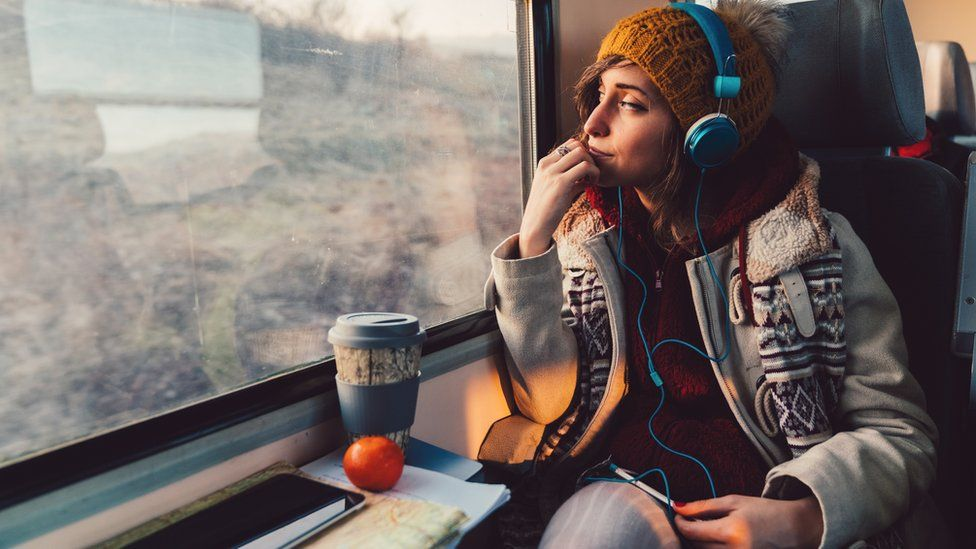 Young woman listening to podcast on a train