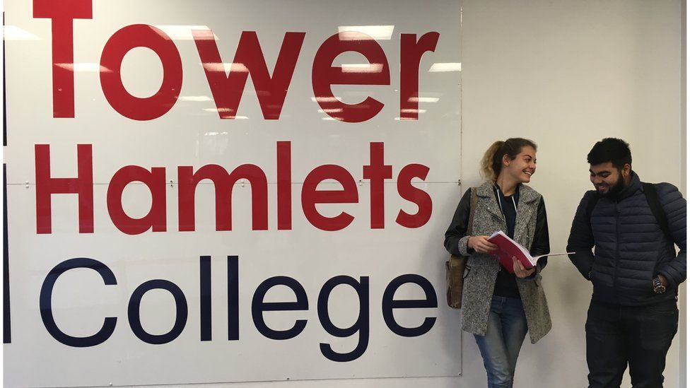 Two students stand by the entrance sign of Tower Hamlets College
