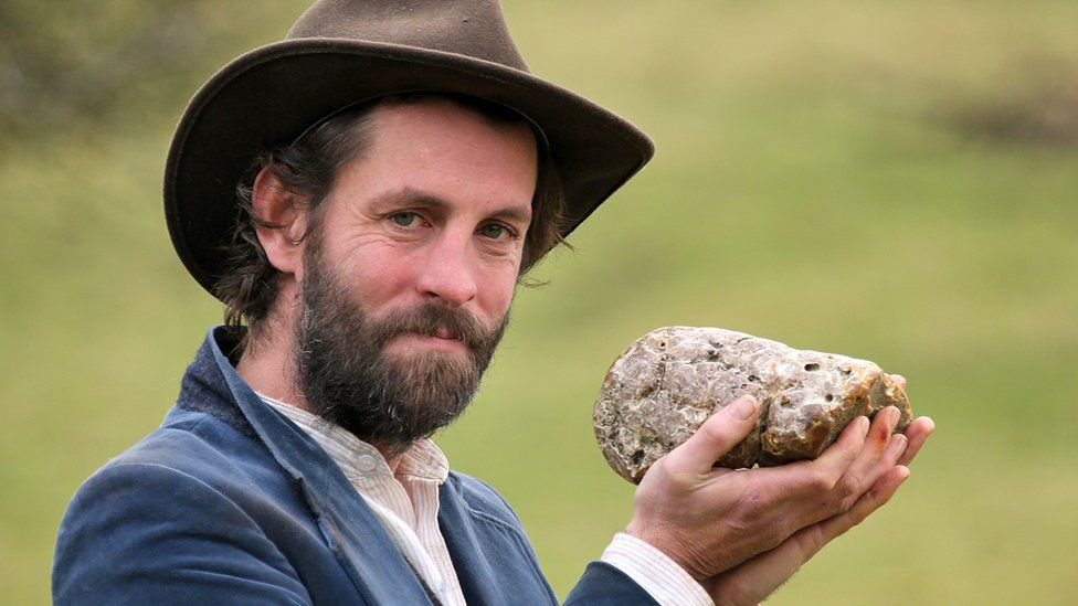 man holding whale dung stone