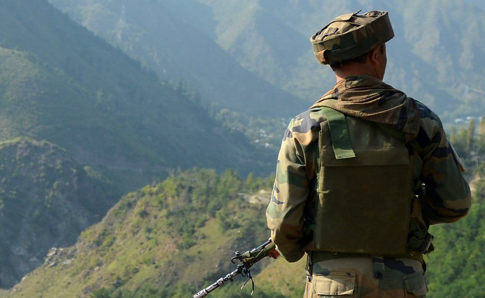 An Indian army soldier looks towards the site of a gun battle between Indian army soldiers and rebels inside an army brigade headquarters near the border with Pakistan, known as the Line of Control, in Uri. Taken on 18 September 2016.