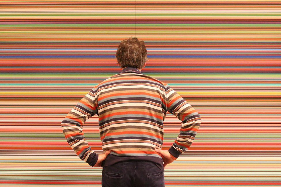 A man in a hooped top looks at hooped artwork.