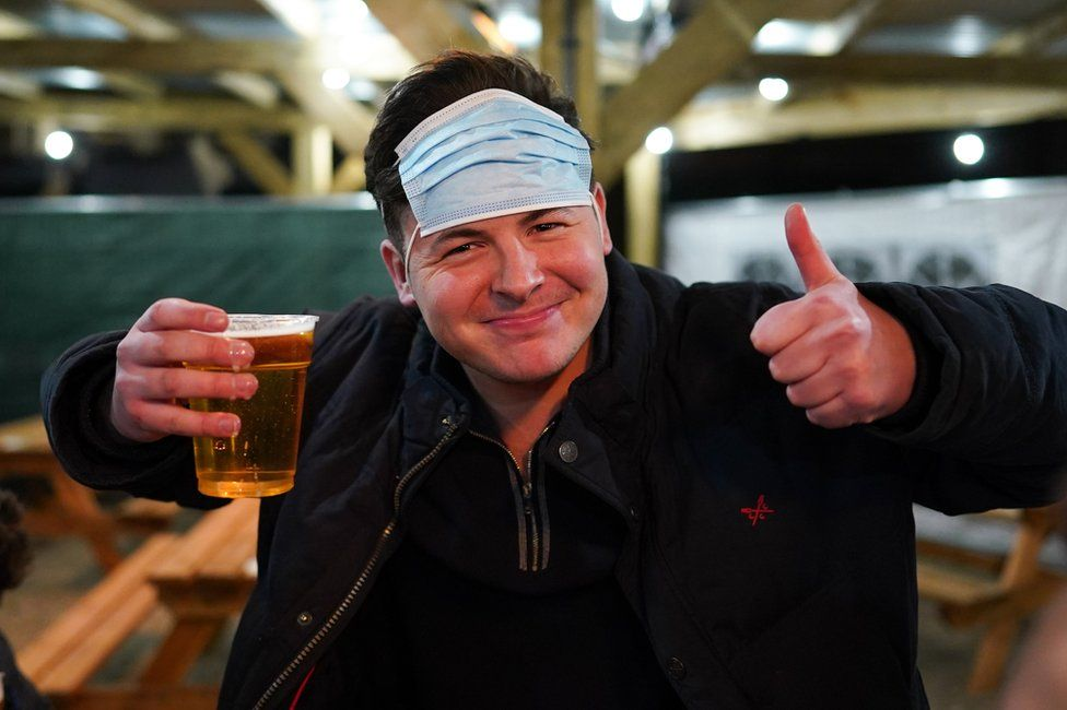 A man holds a pint of beer with a face mask on his head