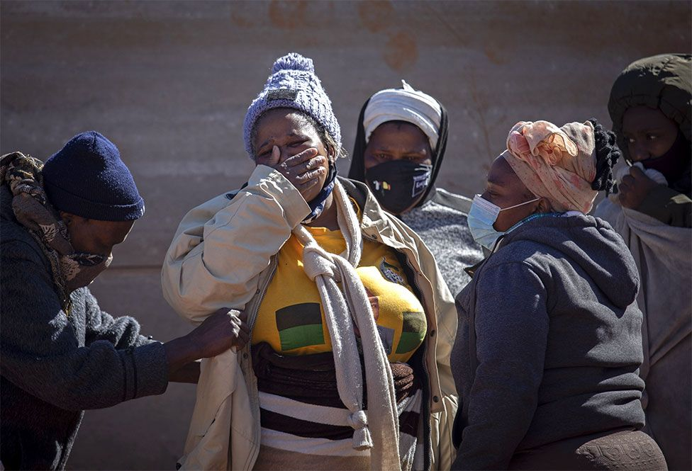 Relatives of a deceased looter mourn next to his body after he looted goods from shops in the area, Johannesburg, South Africa, on 13 July 2021