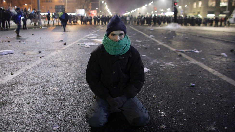 A protestor sits on the ground following scuffles between protestors and Romanian police at a demonstration in Bucharest, Romania