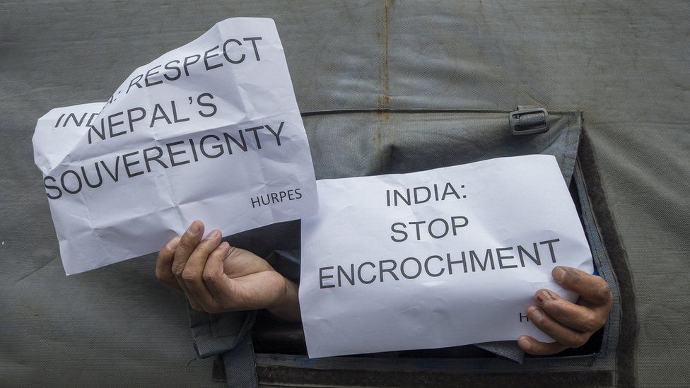 Activists affiliated with Human Rights and Peace Society Nepal hold signs in the back of a police vehicle during an anti-Indian-government protest at the Indian Embassy in Kathmandu, Nepal, 12 May 2020.