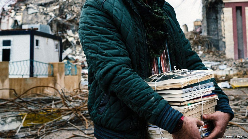 An Iraqi students carries books away from the ruins of the university