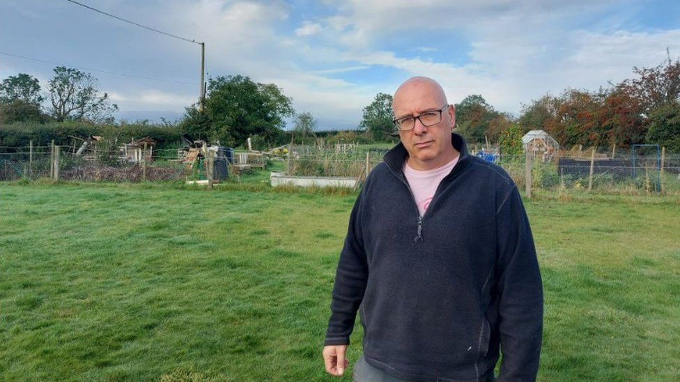 Photo of Mr Plummer standing in front of land at centre of dispute