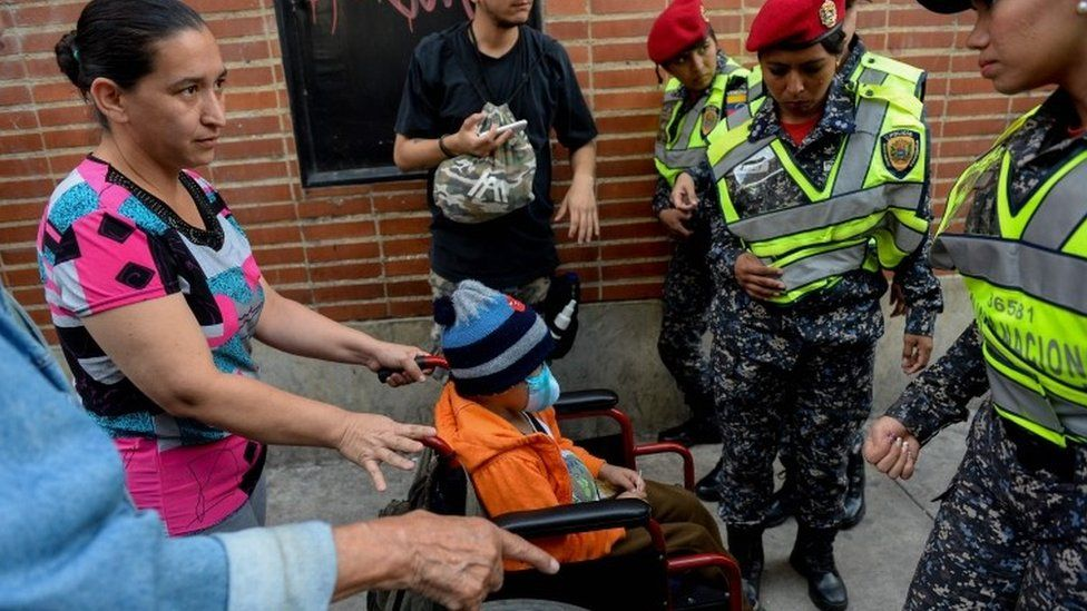 """A woman pushing a wheelchair with a child at a health workers protest outside the """"Dr J M de los Rios"""" Children's Hospital in Caracas 16 August 2018."""
