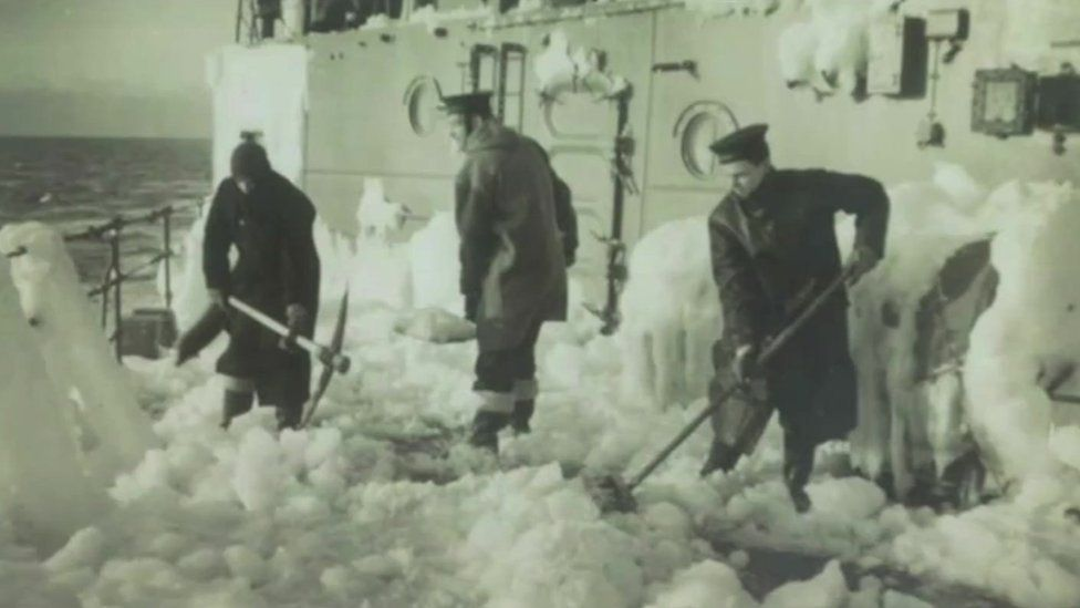 men shovelling ice from ship deck