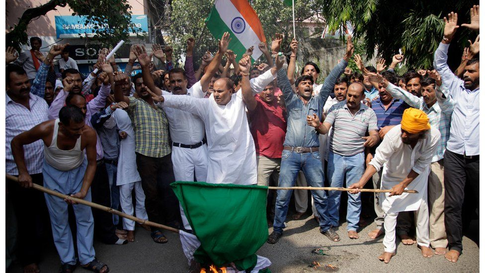 Indian nationalist activists burn a Pakistani flag in Jammu, India, as they protest the attack on Sunday 18 September.